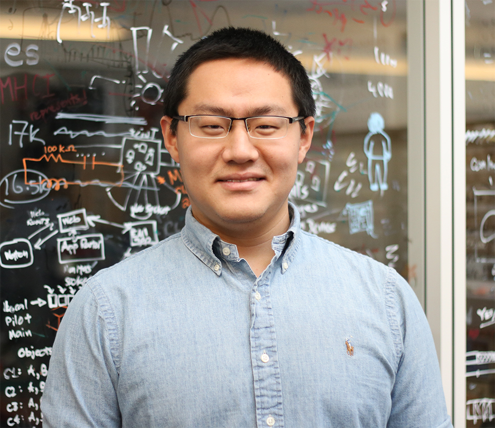 Anhong Guo wearing a light blue shirt standing in front of a glass wall with drawings.