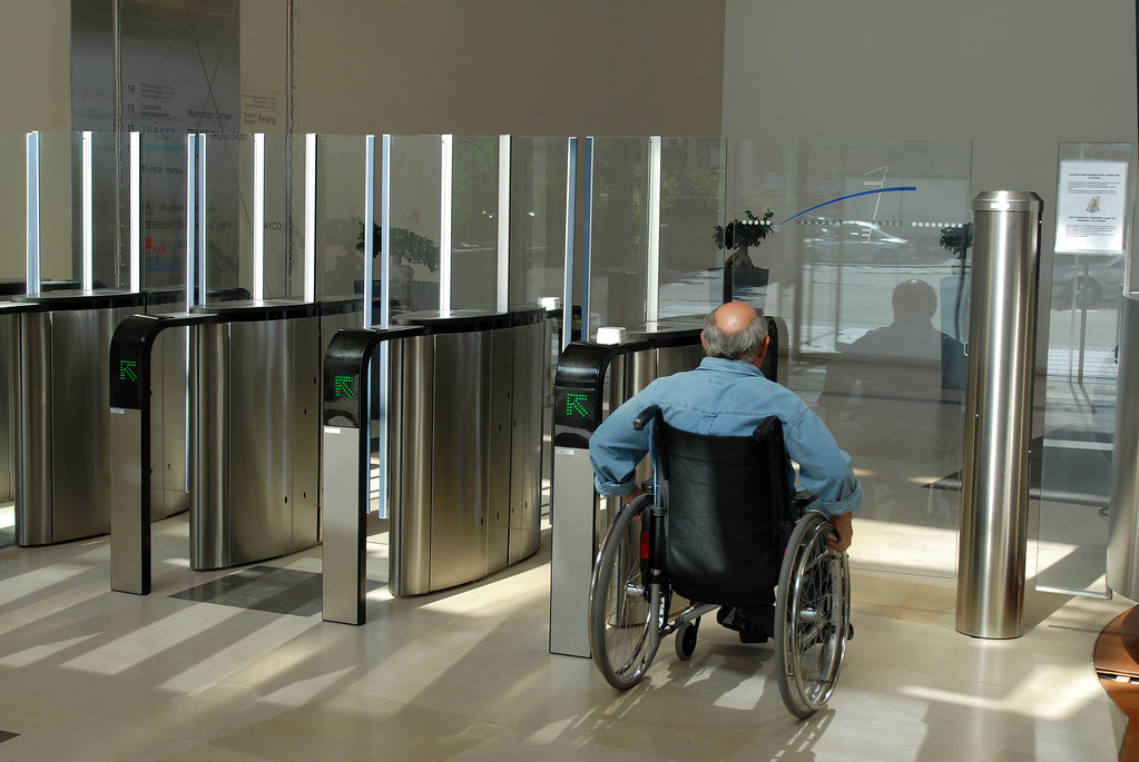Image of a person in a wheelchair in front of a swing gate
