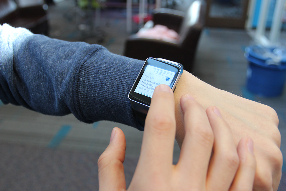 A user working on a document on a smartwatch using WearWrite, by leveraging a crowd to help trans­late their ideas into text.