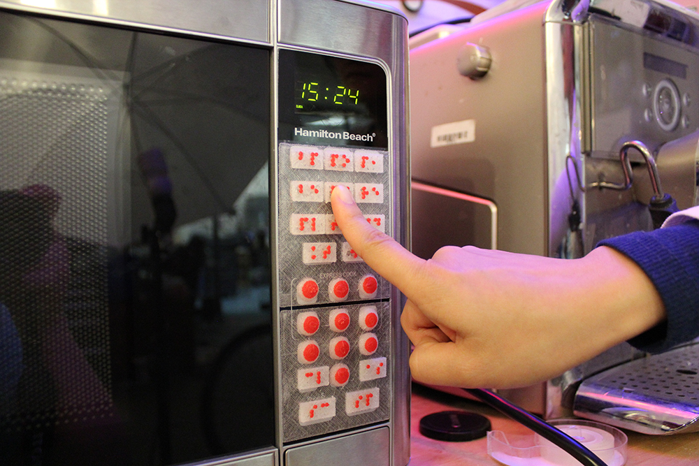 A user accessing the microwave augmented with tactile overlays generated by Facade.