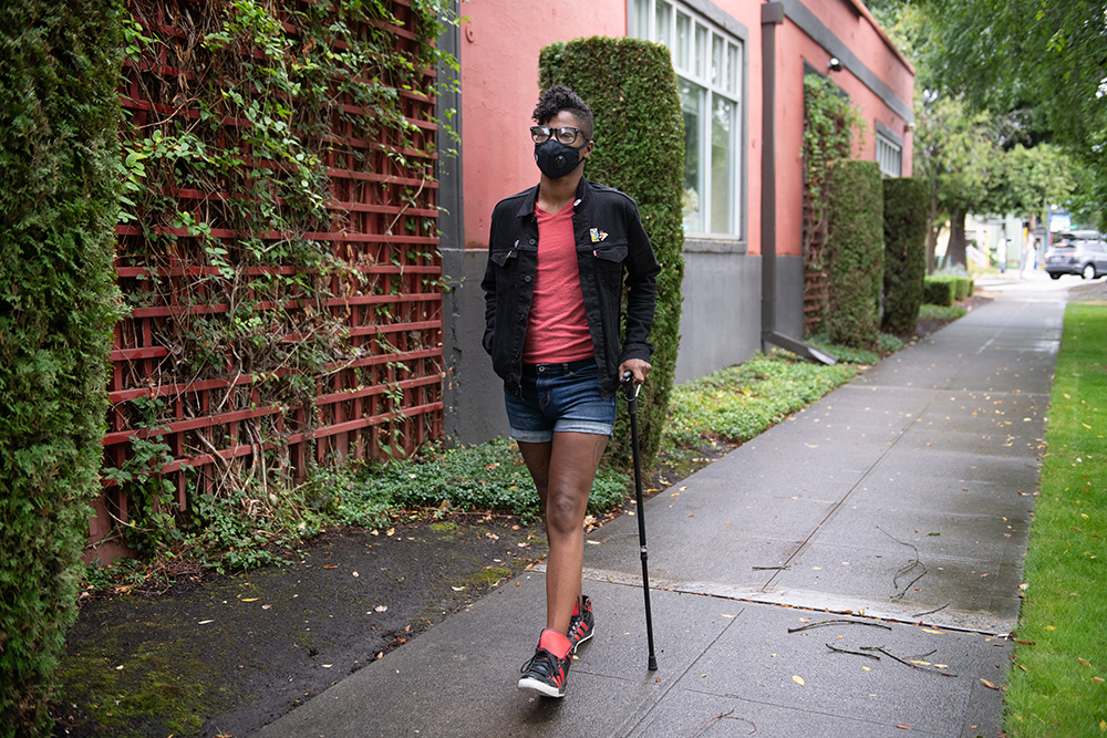 Leila, a black, non-binary person with a filtering face mask walks down a neighborhood street with one hand in their pocket and the other hand on their cane. They have a short mohawk and are wearing a jacket, shorts, tennis shoes, and glasses.