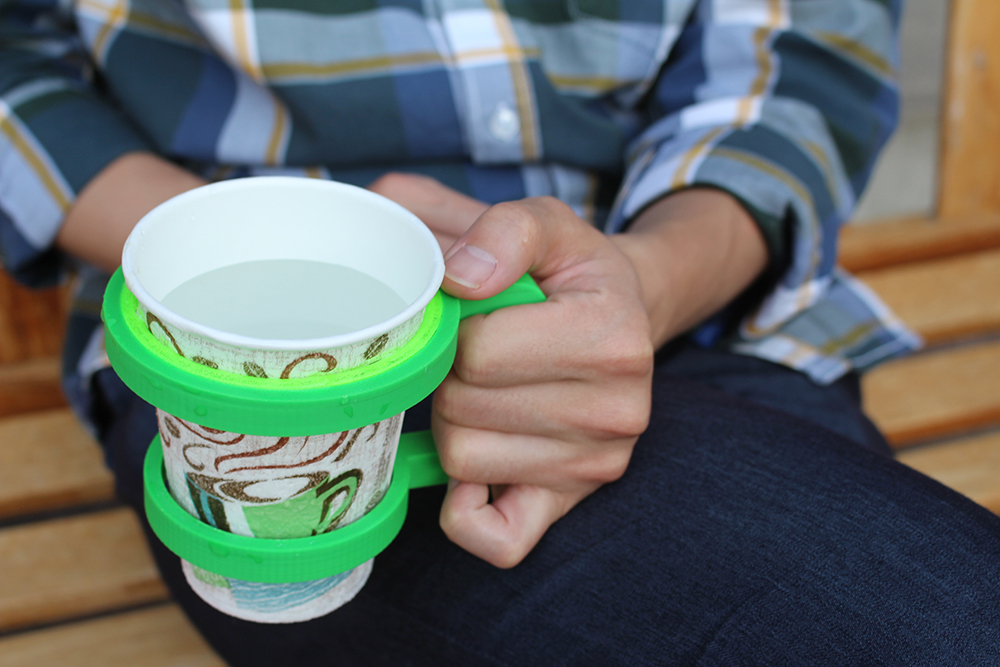 A user holding a 3D-printed cup holder augmented with a flexible ring generated using our flexible buffers technique.
