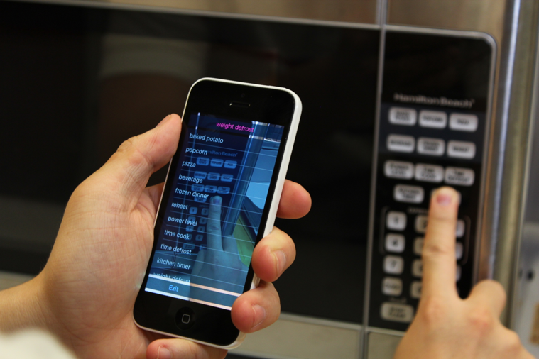 The user is holding the phone in portrait mode with one hand, and aiming the camera towards an inaccessible microwave control panel. The user's other hand is exploring on the panel. The VizLens iOS app is providing audio feedback and guidance to the user.