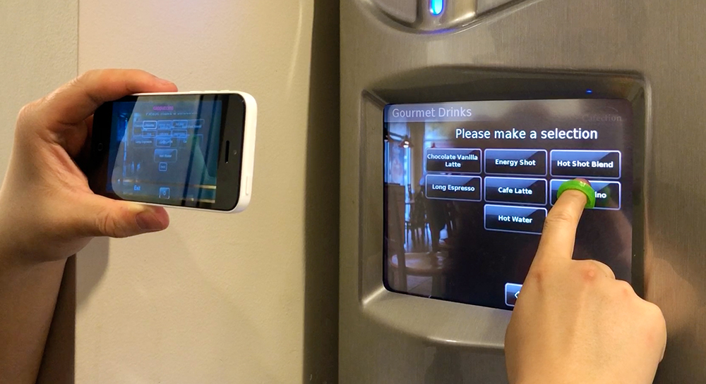 The user is holding the phone in landscape mode with one hand, and aiming the camera towards a touchscreen coffee machine. The user's other hand is wearing a fingercap exploring on the screen. The StateLens iOS app is providing audio guidance to the user.